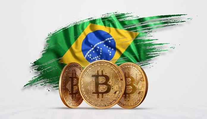 Bandeira do Brasil atrás de moedas físicas do Bitcoin